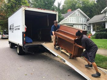 Two young men slide a piano down a moving truck ramp